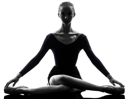 bailarina de ballet: una mujer caucásica joven bailarina de ballet bailarina estiramiento de calentamiento en el estudio de la silueta en el fondo blanco