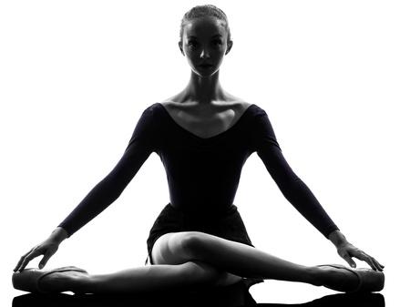 sagoma ballerina: uno caucasica giovane donna ballerina ballerino si estende riscaldamento in studio silhouette su sfondo bianco