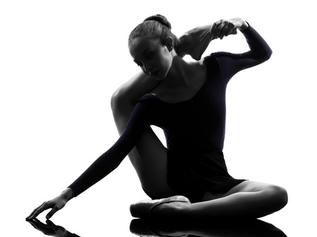 one caucasian young woman ballerina ballet dancer stretching warming up in silhouette studio on white background Stock Photo - 15480196