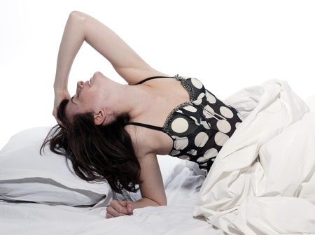 young woman in a white sheet bed on white  stretching photo