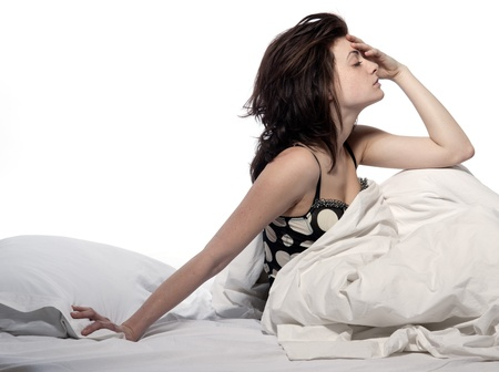 one sheet: one young woman in bed awakening tired insomnia hangover  in a white sheet bed on white background Stock Photo