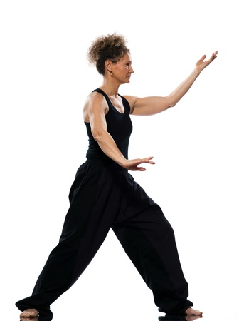 mature woman praticing tai chi chuan in studio on isolated white background photo