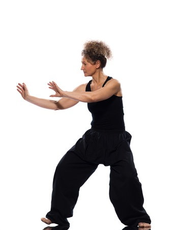 chi kung: mature woman praticing tai chi chuan in studio on isolated white background