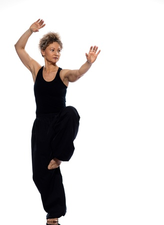 tai: mature woman praticing tai chi chuan in studio on isolated white background