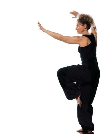 taichi: mature woman praticing tai chi chuan in studio on isolated white background