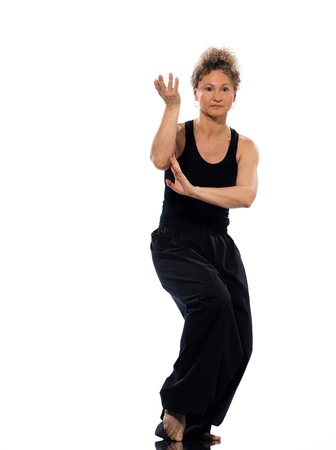 chuan: mature woman praticing tai chi chuan in studio on isolated white background