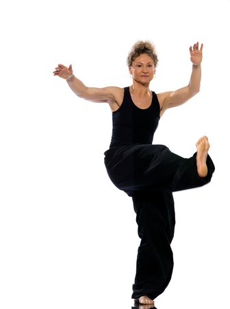 girl kick: mature woman praticing tai chi chuan in studio on isolated white background