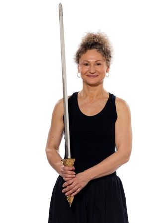 mature woman praticing tai chi chuan with sword in studio on isolated white background photo