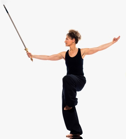 tai chi: mature woman praticing tai chi chuan with sword in studio on isolated white background
