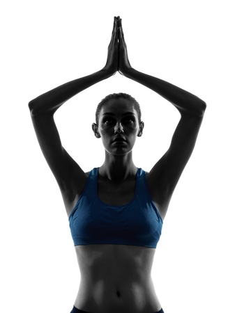 one caucasian woman exercising yoga hands joined  portrait in silhouette studio isolated on white background photo