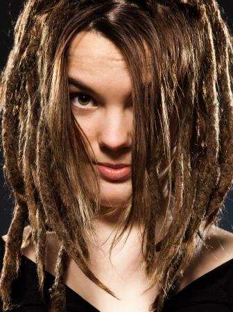 dreadlocks: estudio de disparo retratos de una joven mujer rubia caucásica con dreadlocks en fondo negro