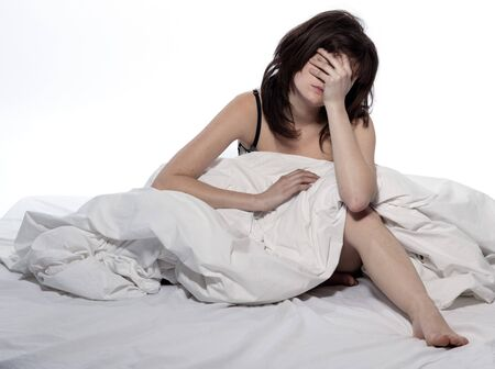 hangover: one young woman in bed awakening tired insomnia hangover  in a white sheet bed on white background Stock Photo