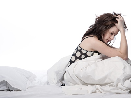 one young woman in bed awakening tired insomnia hangover  in a white sheet bed on white background Stock Photo - 15479283