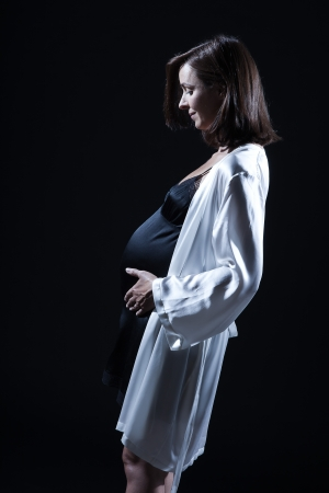 beautiful smiling caucasian pregnant  woman portraitt   touching her belly in nightie on studio isolated black background Stock Photo - 15640894