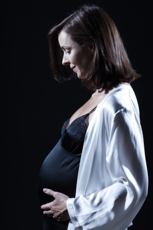 beautiful smiling caucasian pregnant  woman portraitt   touching her belly in nightie on studio isolated black background Stock Photo - 15640907
