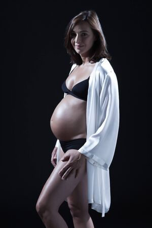 beautiful smiling caucasian pregnant  woman portraitt  in nightie on studio isolated black background photo