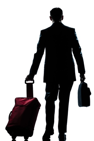 business traveler: rear view one caucasian business traveler man walking with suitcase  full length silhouette in studio isolated white background Stock Photo
