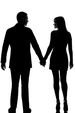 fashionable couple: rear view one lovers caucasian couple man and woman walking hand in hand in studio silhouette isolated on white background