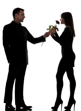 one caucasian lovers couple man offering rose flower and woman smelling in studio silhouette isolated on white background