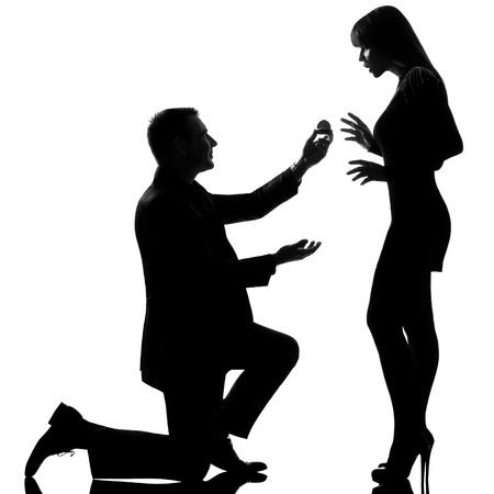 arrodillarse: un hombre cauc�sico pareja arrodillada oferta anillo de compromiso y una mujer sorprendida en estudio, silueta, aislado sobre fondo blanco