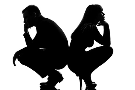 pouting: one sad caucasian couple man and woman crouching back to back in studio silhouette isolated on white background