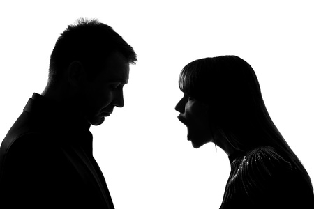 angry couple: one caucasian couple man and woman face to face screaming shouting dipute in studio silhouette isolated on white background Stock Photo