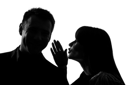 secret love: one caucasian couple man and woman  whispering at ear in studio silhouette isolated on white background