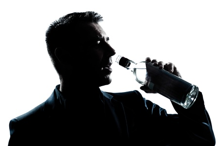 one caucasian man portrait silhouette drunk puring empty alcohol botlle in studio isolated white background photo