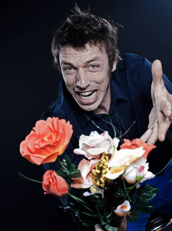 studio portrait on black background of a funny expressive caucasian man offering flowers anger photo