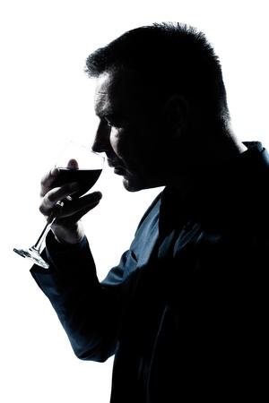 isol� sur fond blanc: un portrait homme caucasien silhouette sentant verre de vin rouge en studio isol� sur fond blanc