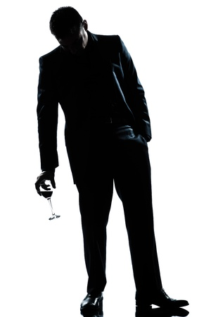 one caucasian man full length silhouette  drunk holding a glass of red wine in studio isolated white background Stock Photo - 15639298