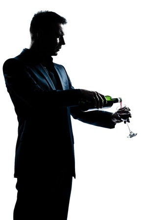 one caucasian man portrait pouring wine in a glass silhouette in studio isolated white background photo