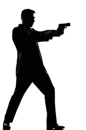 man with gun: one caucasian  spy criminal policeman detective man aiming shooting gun  full length silhouette in studio isolated white background