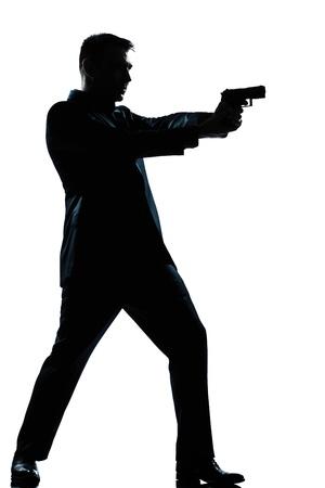 isol� sur fond blanc: un espion caucasien homme criminel policier d�tective pointage du canon de tir longueur silhouette compl�te en studio isol� sur fond blanc