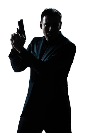 isolated on the white background: one caucasian spy criminal policeman detective man holding gun portrait silhouette in studio isolated white background Stock Photo