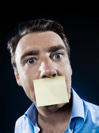 caucasian man mouth shut by a note paper portrait isolated studio on black background photo