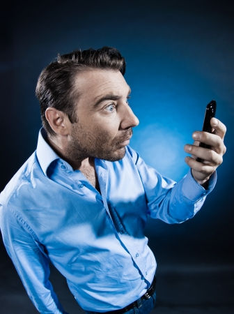 caucasian man unshaven looking at cellphone amazed portrait isolated studio on black background photo