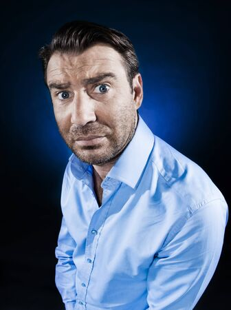 sulk: caucasian man frown sulk unshaven portrait isolated studio on black background