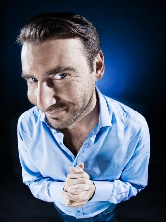 sneaky: caucasian man beg malicious smile unshaven portrait isolated studio on black background