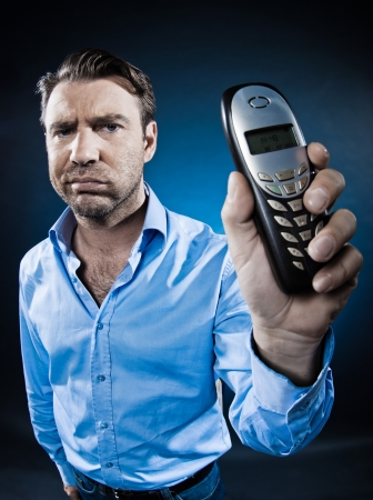 fed up: caucasian man show phone sulk unshaven portrait isolated studio on black background Stock Photo