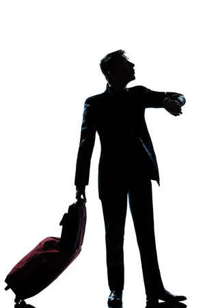 one caucasian  business traveler man checking the time full length silhouette in studio isolated on white background photo