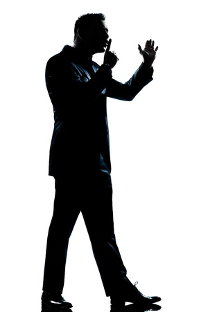 one caucasian man menace hushing for silence full length silhouette in studio isolated white background photo