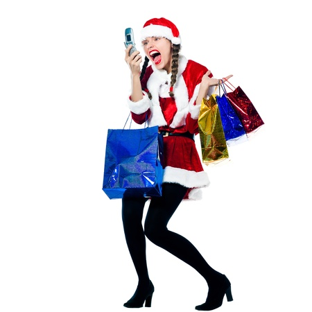 one woman dressed as santa claus carrying screaming on the telephone christmas bags  on studio isolated white background photo