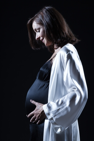 beautiful smiling caucasian pregnant  woman portraitt   touching her belly in nightie on studio isolated black background Stock Photo - 15800750