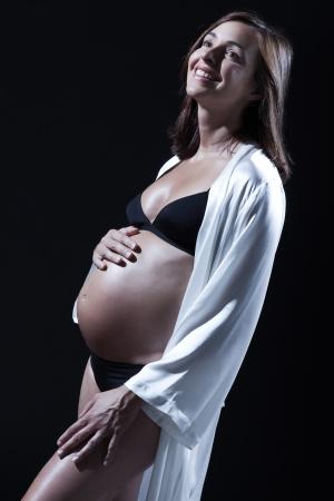 beautiful smiling caucasian pregnant  woman portraitt  in nightie on studio isolated black background Stock Photo - 15800699