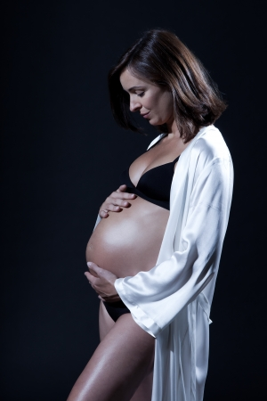 beautiful smiling caucasian pregnant  woman portraitt   touching her belly in nightie on studio isolated black background Stock Photo - 15800706