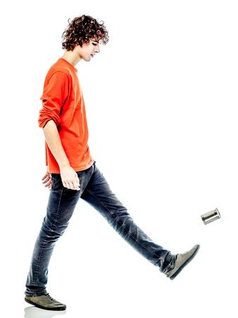 persona caminando: un hombre joven caucásico patadas estaño lata triste vista lateral del agujero en estudio de fondo blanco