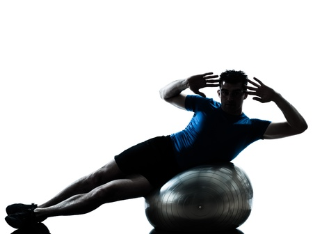 body silhouette: one caucasian man exercising workout fitness ball in silhouette studio  isolated on white background