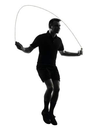 one man exercising jumping rope  in studio silhouette isolated on white background photo