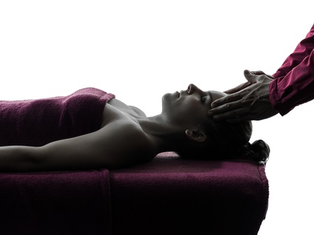 massage table: woman receiving head massage in silhouette studio on white background
